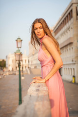 Beautiful girl in pink dress in Venice