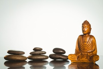 Wooden buddha statue with balancing pebbles
