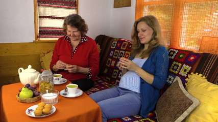 Senior woman and pregnant granddaughter eat sweets with tea