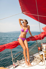 beautiful model girl on yacht with red sails