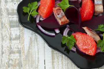 dish with a salad of herring, beetroot and grapefruit on a woode