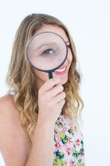 Smiling woman holding magnifying glass