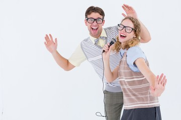 Geeky hipster couple singing into a microphone