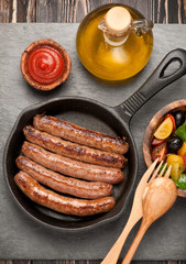 grilled sausages in a pan and vegetable salad. top view