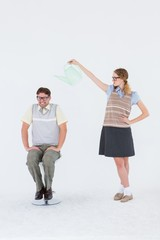 Geeky hipster holding watering can above her boyfriend