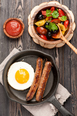 grilled sausages in frying pan and fried eggs