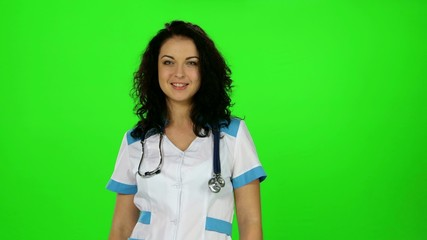 Beautiful nurse in a white coat standing, smiles and puts