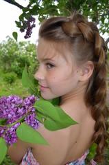 Портрет молодой девушки на фоне цветения сирени