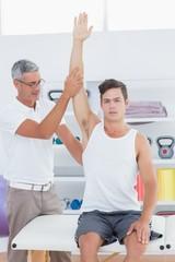 Doctor raising a young man arm