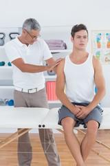 Doctor examining his patient shoulder