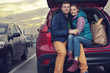 Happy couple sitting at car trunk after shopping