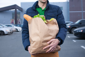 closeup of man hoplding a shopping bag
