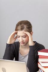 Studentin mit Laptop und Büchern, gestresst