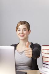 Studentin mit Laptop und Büchern, Daumen hoch