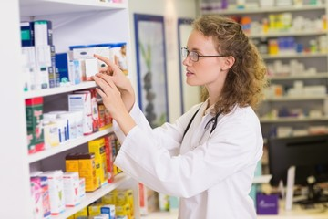 smiling pharmacist taking jar from shelf