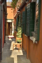 Orange alley in Burano, a fisher island of Venice, Italy