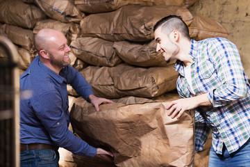 Two loaders handling sacks
