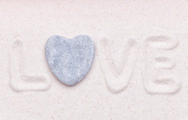 The word love is written in the white sand with a heart shaped s