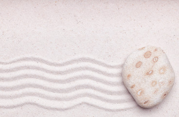 Zen garden with a white spotted rock and wave pattern in the san