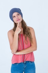 Thoughtful woman wearing hat with finger on chin
