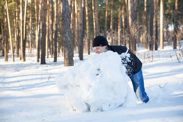 man rolls large snow globe