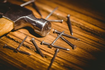 Hammer and nails laid out on table