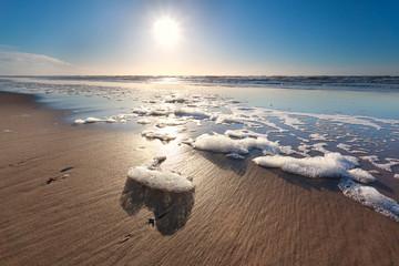 sunshine over North sea waves on beach