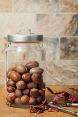 Glass jar of nuts in the shell with marble tile backsplash