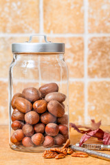 Glass jar of nuts in the shell in country kitchen setting