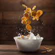 Falling corn flakes with milk splash on wood - 80275162