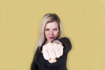 Young woman showing strength (studio, fist, yellow, background)