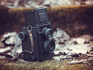 Vintage stylized photo of retro film camera on old stairs covere