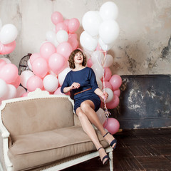 young woman on the sofa  in a room full of inflatable balloons