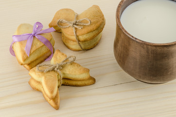 Set of cookies and cap of milk on wooden background