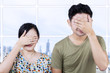 Asian couple cover faces in apartment