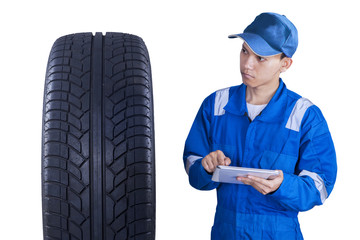 Asian mechanic controls a tire with tablet