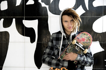 portrait of young guy  with skate and rasta hair