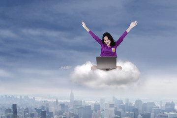 Cheerful student with laptop on cloud