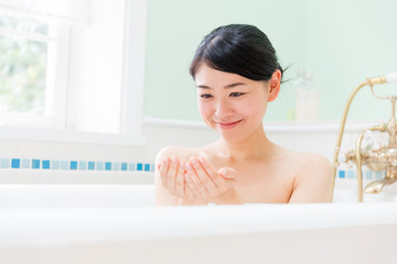 young asian woman relaxing in the bathroom