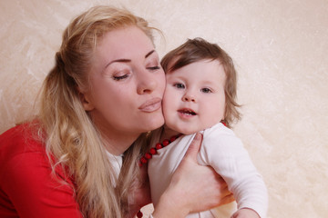 Mother cheek to cheek with one year baby girl