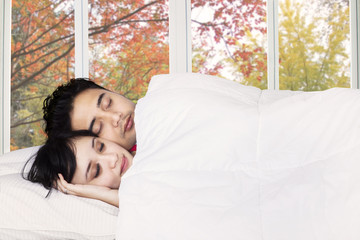 Couple sleeping together on bedroom
