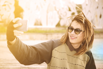 young rasta guy outdoor taking selfie with smart phone with a wa