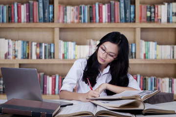 Female student concentrate studying in library