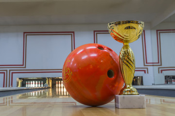 Closeup of blue bowling ball near golden trophy on the floor
