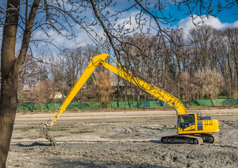 Yellow excavator doing lake cleaning and maintenance services