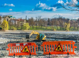 Yellow excavator doing lake cleaning