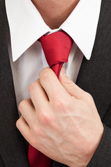 Businessman grabbing tie