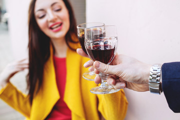 Woman clinking red wine glass with man outdoors