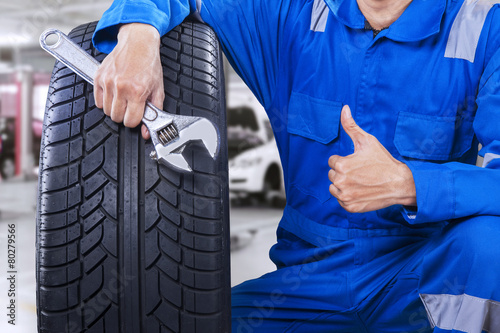 canvas print picture Male mechanic showing thumb up in workshop