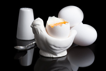 cooked soft boiled egg, salt shaker and spoon